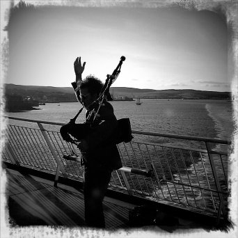 Calum piping on the boat from Shteland b and w